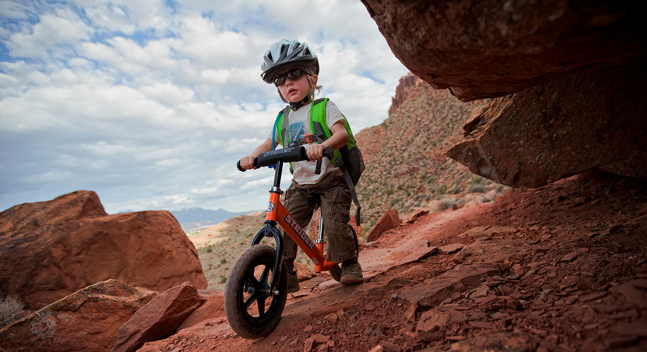 Toddler riding bike on Pipe Dream Trail near Moab